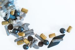 Variety of salmiakki candies spilling out of overturned jar onto solid white background stock photo