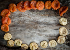 Assorted dried apricots and figs on aged wood with copy space. Royalty Free Stock Images