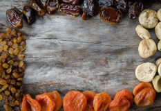 Assorted dried apricots, figs, dates and raisins on aged wood with copy space. Stock Images