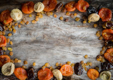 Assorted dried apricots, figs, dates and raisins on aged wood with copy space. Royalty Free Stock Photography