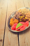 Assorted dry fruits and nuts on plate over wooden background Stock Images