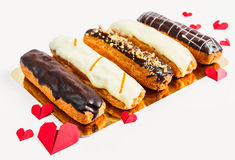 Assorted eclairs on a gold substrate on a white background Royalty Free Stock Image