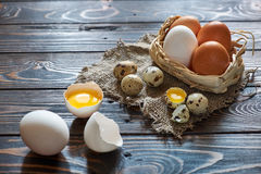 Assorted eggs rural composition. With solar lighting on wood background Royalty Free Stock Photo