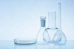 Assorted empty laboratory glassware, test-tubes. Blue tone medical background. Copy space Stock Photo