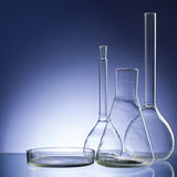 Assorted empty laboratory glassware, test-tubes. Blue tone medical background. Copy space Stock Photos