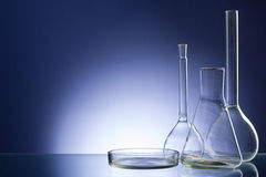 Assorted empty laboratory glassware, test-tubes. Blue tone medical background. Copy space Stock Photography
