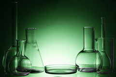 Assorted empty laboratory glassware, test-tubes. Green tone medical background. Copy space Stock Image