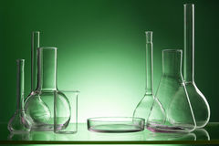 Assorted empty laboratory glassware, test-tubes. Green tone medical background. Copy space Royalty Free Stock Images