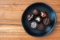 Assorted fancy chocolate candy on a rustic black plate on a wood background. For Valentine's Day royalty free stock photos