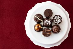 Assorted fancy chocolate candy on a white cake stand on a red background. For Valentine's Day royalty free stock photos