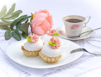 Assorted fancy gourmet cupcakes on a plate. Cupcakes with beautiful decoration over white vintage lace background. Surrounded by flowers and cup of coffee Stock Photography