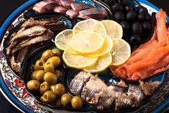 Assorted fish on a plate on a dark background.  Stock Photography