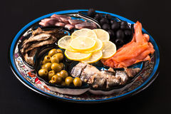 Assorted fish on a plate on a dark background.  Stock Images