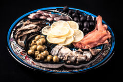 Assorted fish on a plate on a dark background.  Royalty Free Stock Photography