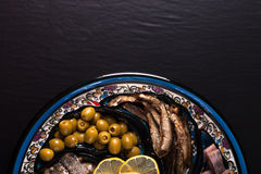 Assorted fish on a plate on a dark background. With space for te Royalty Free Stock Photo