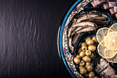 Assorted fish on a plate on a dark background. With space for te Royalty Free Stock Images