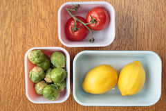 Assorted food in bowls. Green brussel sprouts, ripe red tomatoes and yellow lemon fruit in bowls from above Stock Images