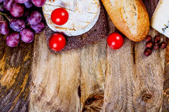 Assorted food ingredients. Cheese, bread, tomatoes and grapes and vertical copyspace ready to be filled with some text Stock Photo