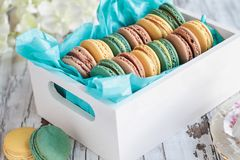 Assorted French Macarons in a Box. Assortment of fresh french macarons packaged in a pretty white wooden box with blue tissue on a white rustic table royalty free stock images