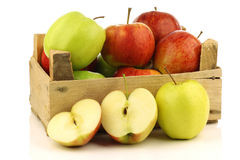 Assorted fresh apples in a wooden crate. On a white background Stock Photos