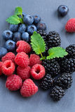 Assorted fresh berries on a black background, close-up Royalty Free Stock Images