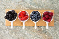 Assorted fresh berries in taster dishes. Viewed from above lined up on a wooden board on a stone kitchen counter with blackberries, sliced strawberry Stock Photography
