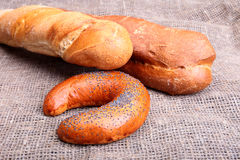 Assorted fresh breads isolated on old sackcloth. Stock Image