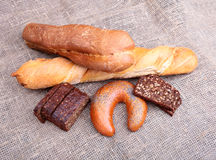 Assorted fresh breads isolated on old sackcloth. Stock Photography