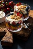 Assorted fresh fruit with custard in glasses on dark background Stock Photo