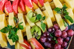 Assorted fresh fruits on plate. Apple, grapes, kiwi, pineapple, grapefruit, orange, banana and mint on wooden table. Selective focus royalty free stock photo