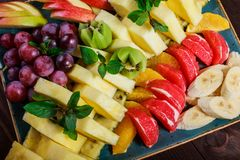 Assorted fresh fruits on plate. Apple, grapes, kiwi, pineapple, grapefruit, orange, banana and mint on wooden table. Selective focus stock image