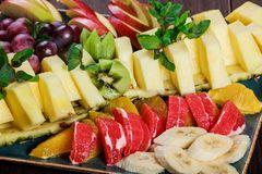 Assorted fresh fruits on plate. Apple, grapes, kiwi, pineapple, grapefruit, orange, banana and mint on wooden table. Selective focus stock photography