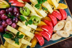 Assorted fresh fruits on plate. Apple, grapes, kiwi, pineapple, grapefruit, orange, banana and mint on wooden table. Selective focus royalty free stock photography