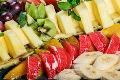 Assorted fresh fruits on plate. Apple, grapes, kiwi, pineapple, grapefruit, orange, banana and mint on wooden table. Selective focus stock photos