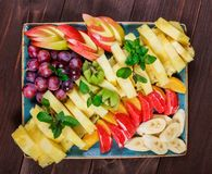 Assorted fresh fruits on plate. Apple, grapes, kiwi, pineapple, grapefruit, orange, banana and mint on wooden table. Top view royalty free stock images