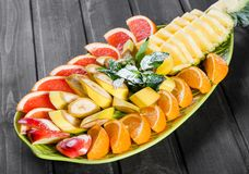Assorted fresh fruits on plate. Apple, orange, pineapple, grapefruit, banana and mint on dark background. Top view royalty free stock photos