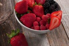 Assorted fresh juicy berries in bowls. Healthy Eating and Diet. Assorted with summer berries like strawberries, raspberries, blueberries Royalty Free Stock Photos