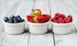 Assorted fresh juicy berries in three tiny bowls Royalty Free Stock Photography
