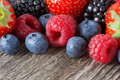 Assorted fresh juicy berries on wooden background Stock Photos