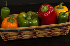 Assorted fresh peppers in small basket Royalty Free Stock Image