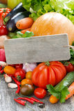 Assorted fresh seasonal vegetables and a wooden nameplate. Vertical, close-up Royalty Free Stock Photos