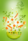 Assorted fresh vegetables falling. Into a green bowl, on light green background royalty free stock photos