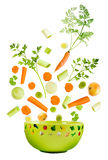 Assorted fresh vegetables falling. Into a green bowl isolated on white background stock photos