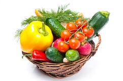 Assorted fresh vegetables and herbs in a wicker basket Royalty Free Stock Photo