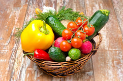 Assorted fresh vegetables and herbs in wicker basket Stock Photo