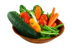 Assorted Fresh Vegetables In A Wooden Bowl. A wooden salad bowl filled with sugar snap peas, mini sweet peppers, plum tomatoes, carrots, cucumber, and bok choy Stock Photo