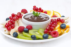 Assorted fruit with chocolate sauce on a plate, close-up Stock Photo