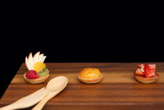Assorted fruit tartlets on wooden board Stock Photos