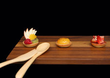Assorted fruit tartlets on wooden board Stock Photography