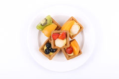 Assorted fruit tarts on round plate Stock Photography